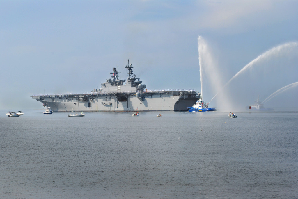Tugboats offer a salute to the amphibious assault ship America (LHA-6) as it sails away from Ingalls Shipbuilding, on Friday, July 11, 2014 (Photo by Shane Scara/HII)