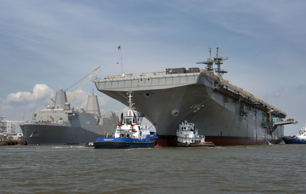Tugboats guide the amphibious assault ship America (LHA-6) to her berthing place at Ingalls Shipbuilding. The Ingalls-built amphibious transport dock Arlington (LPD-24) can be seen in the background