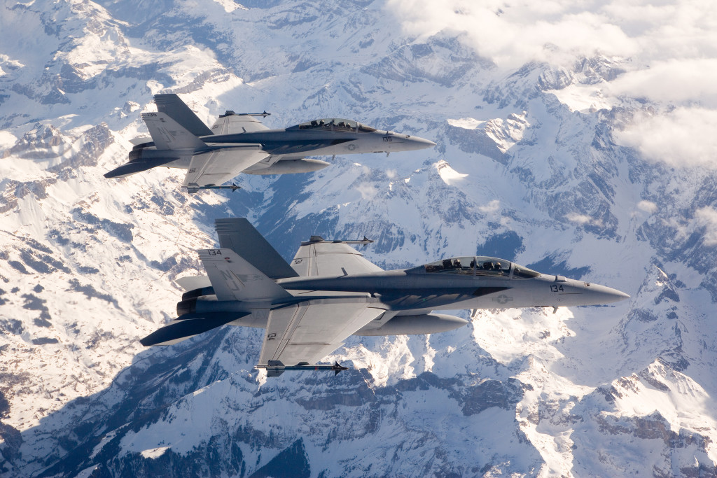 F/A-18E/F Super Hornets in flight over mountains, snow. In route to India Aero Show.