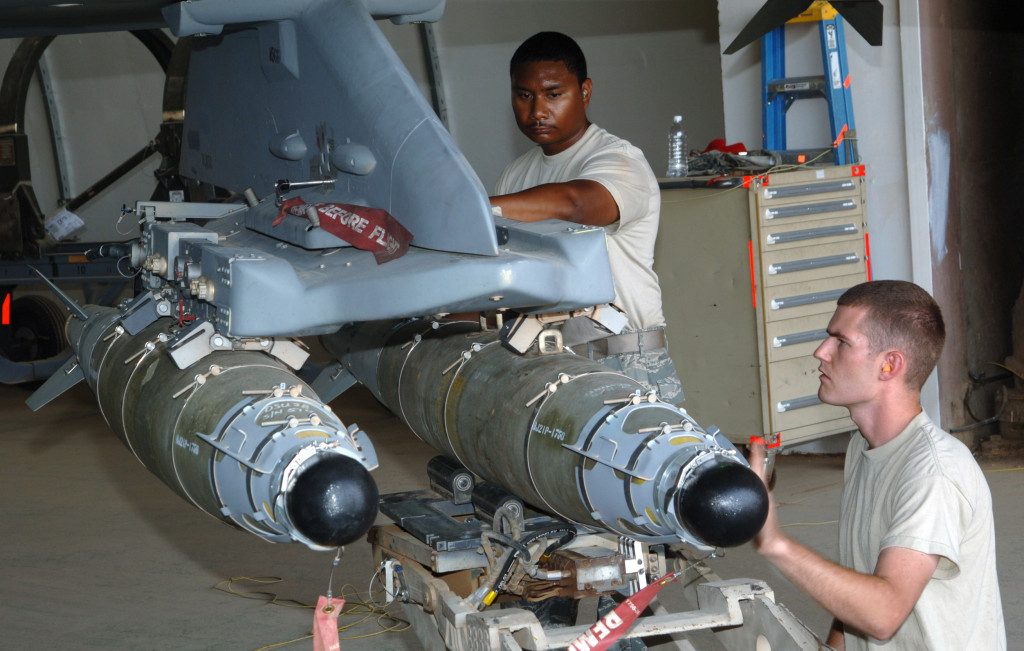 Staff Sgts. Michael Jackson and Anthony Bagen align a 500-pound GBU-54 Laser Joint Direct Attack Munition before connecting it to an F-16 Fighting Falcon