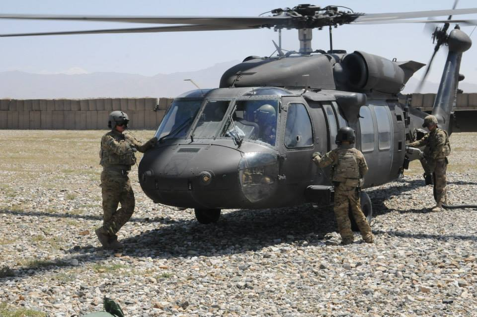 The crew of a UH-60M Black Hawk helicopter from 2nd Battalion (Assault), 10th Combat Aviation Brigade, Task Force Falcon, wait as a petroleum supply specialist assigned to E Company, 2nd Battalion (Assault), 10th Combat Aviation Brigade refuels their helicopter Aug. 20, at forward Operating Base Shank, Afghanistan