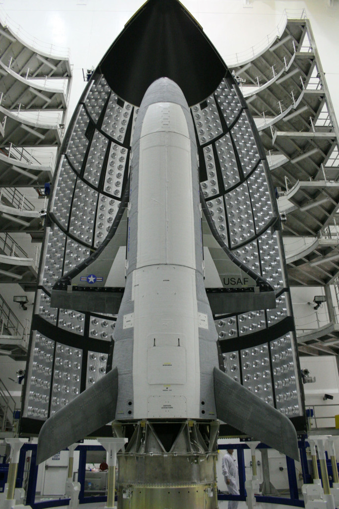 The first X-37B Orbital Test Vehicle waits in the encapsulation cell of the Evolved Expendable Launch vehicle April 5, 2010, at the Astrotech facility in Titusville, Florida. Half of the Atlas V five-meter fairing is visible in the background. The Hall thruster being tested on this flight provide significantly greater specific impulse, or fuel economy and may lead to increased payload carrying capacity and a greater number of on-orbit maneuvers for a spacecraft using Hall thrusters rather than traditional rocket engines (Courtesy photo)