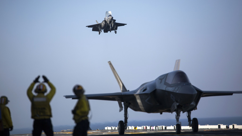 A sailor aboard the USS Wasp (LHD-1) signals to the pilot of an F-35B Lightning II Joint Strike Fighter to land as it arrives for the first phase of operational testing, May 18, 2015. The short take-off, vertical landing capabilities of the F-35B are crucial to the mission of the Marine Corps and necessary for operation aboard a Navy amphibious ship (U.S. Marine Corps photo by Lance Cpl. Remington Hall/Released)