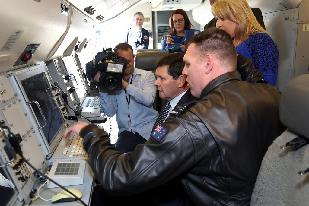 Squadron Leader Andrew Boeree (foreground) shows the Minister for Defence, The Hon Kevin Andrews MP, and the Member for Solomon, Mrs Natasha Griggs MP, the onboard Mission System on the situational display in a No 2 Squadron E-7A Wedgetail aircraft