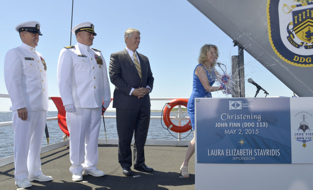 Ship Sponsor Laura Stavridis smashes a bottle of sparkling wine across the bow of the Ingalls-built Aegis destroyer USS John Finn (DDG-113). Also pictured (left to right) are Master Chief Petty Officer of the Navy Michael Stevens; Cmdr. Micheal Wagner, prospective commanding, John Finn; and Ingalls Shipbuilding President Brian Cuccias. Photo by Andrew Young/HII