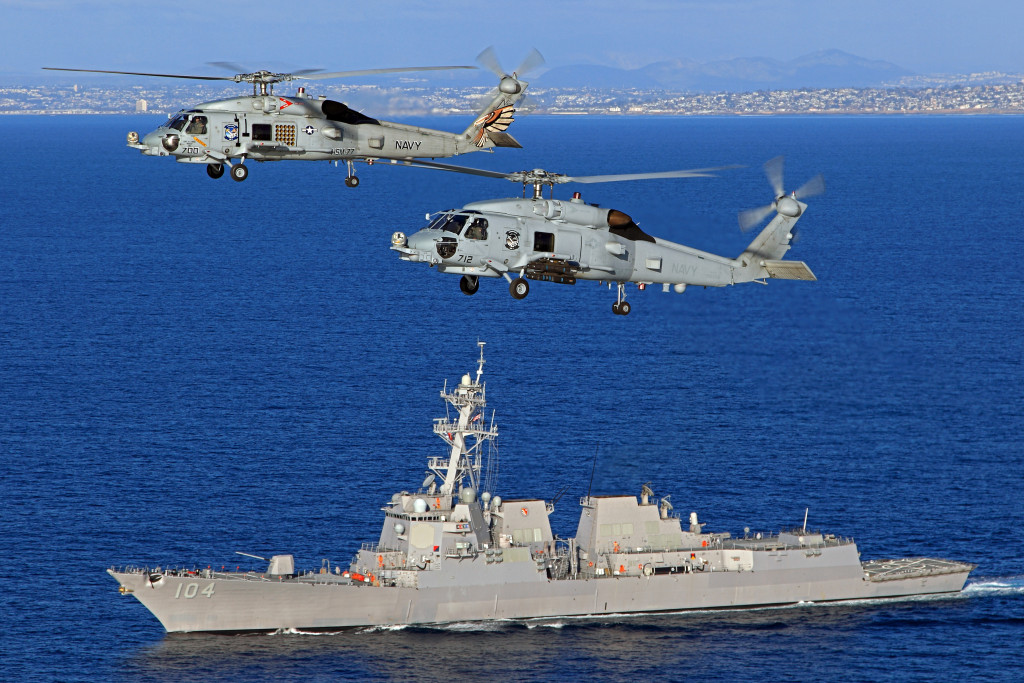A pair of U.S. Navy Sikorsky MH-60R Seahawks, NE 712 166556 and NE 700 166541 of HSM-77 'Sabrehawks', cruise past the USS Sterett (DDG-104) in the Pacific Ocean