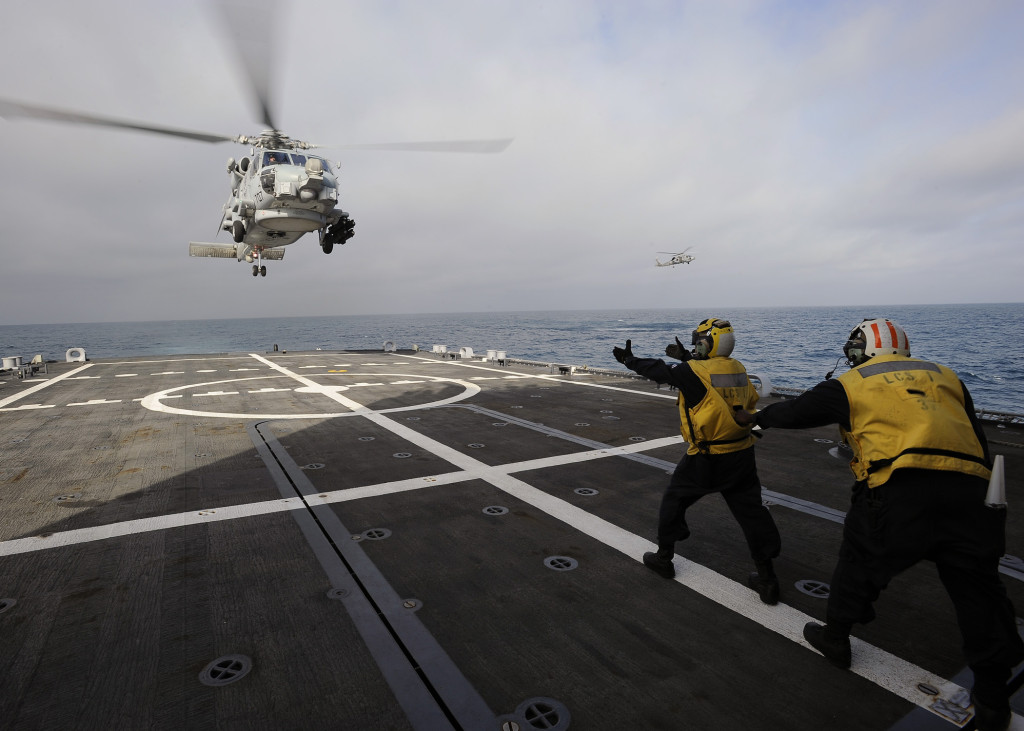 Sailors aboard the littoral combat ship USS Freedom (LCS-1) signal an MH-60R Sea Hawk helicopter assigned to Helicopter Maritime Strike Squadron (HSM) 77 to land during a joint maritime exercise. (U.S. Navy photo by Mass Communication Specialist 3rd Class Sebastian McCormack/Released)