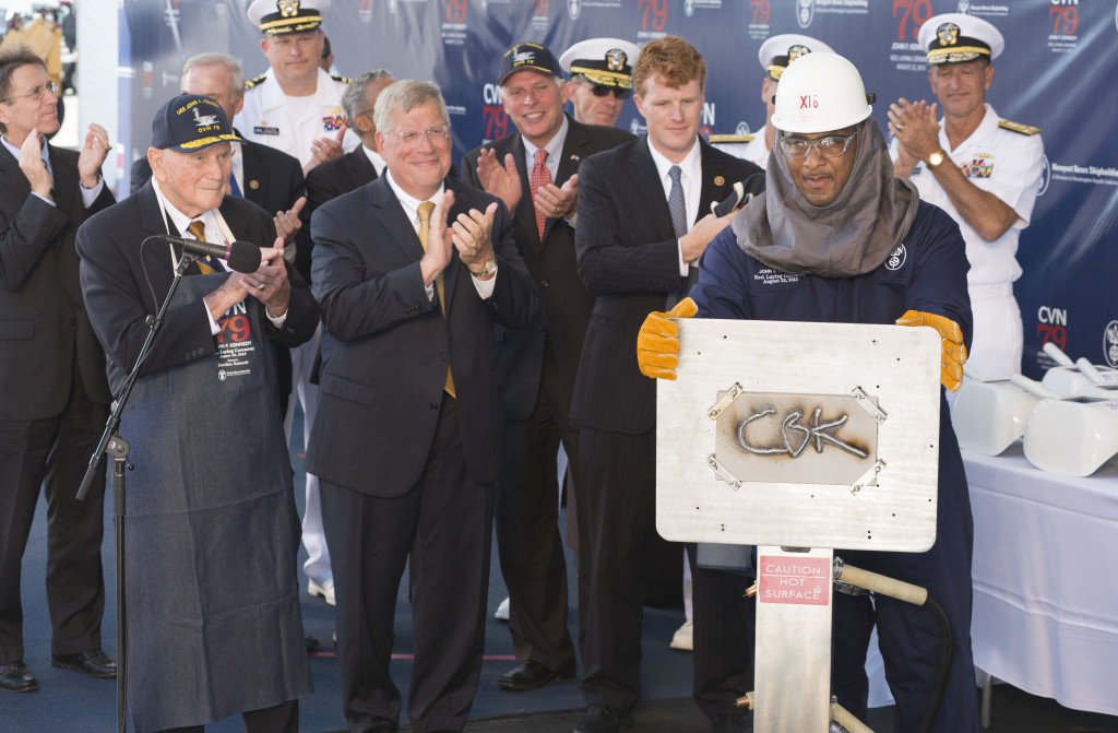 Leon Walston, a Newport News Shipbuilding welder from Massachusetts, displays the welded initials of Caroline Kennedy, the sponsor of the aircraft carrier John F. Kennedy (CVN-79). Also pictured (left to right) are Rear Admiral Earl Yates, the first commanding officer of the aircraft carrier USS John F. Kennedy (CVA-67); Newport News Shipbuilding President Matt Mulherin; Virginia Governor Terry McAuliffe; and Representative Joseph Kennedy (Photo by Chris Oxley/HII)