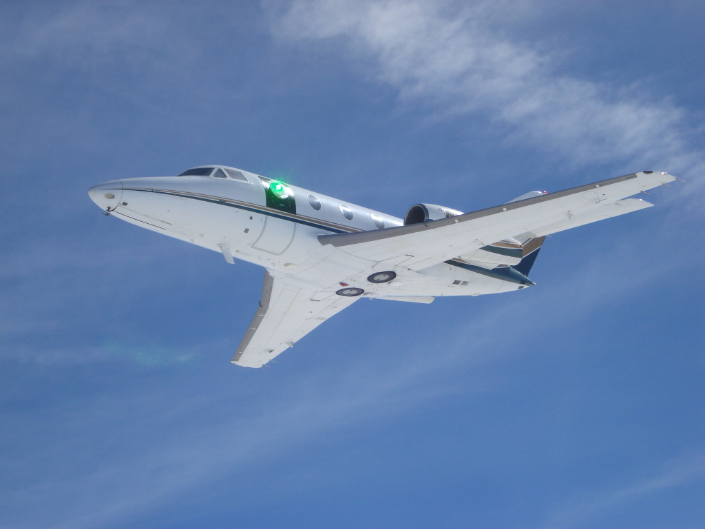 A prototype turret developed by Lockheed Martin for DARPA and AFRL controls and compensates for air flow, paving the way for laser weapon systems on tactical aircraft. Here, a green low-power laser beam passes through the turret on a research aircraft (Photo: Air Force Research Laboratory)