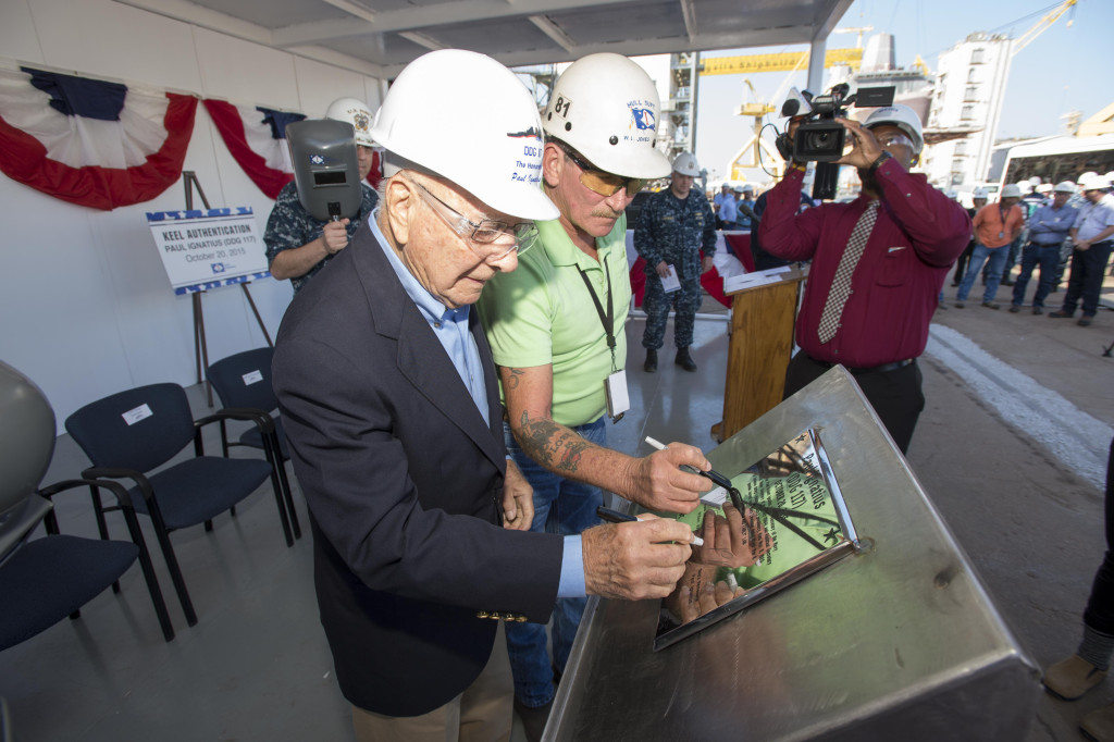 Keel authenticators – ship's namesake Paul Ignatius, left, and Ingalls hull superintendent Bill Jones – sketch their initials on the keel plate to be affixed to the Arleigh Burke-class destroyer Paul Ignatius (DDG-117) (Photo by Lance Davis/HII)