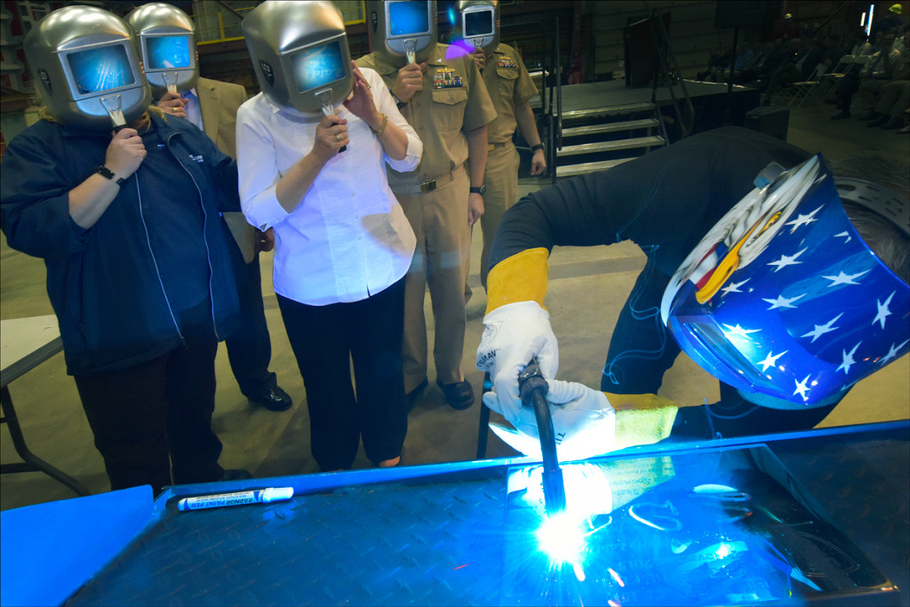 A welder authenticates the keel by welding the initials of LCS-15 sponsor Sharla Tester onto the keel plate. The Keel Laying is the formal recognition of the start of the ship's module construction process (Photo credit: Joseph Mancini, Lockheed Martin)