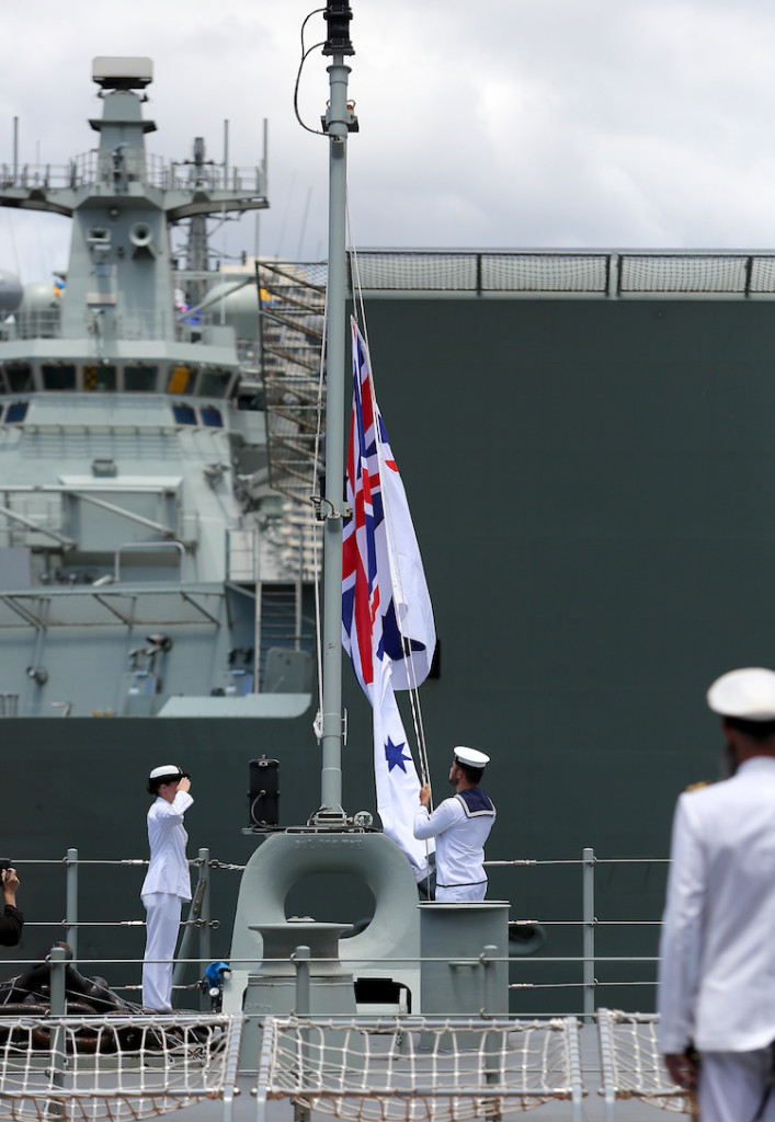 Members of the ship's company of HMAS Adelaide (L01) raise the Australian White Ensign up the ship's mast for the first time, during the Landing Helicopter Dock's Commissioning ceremony