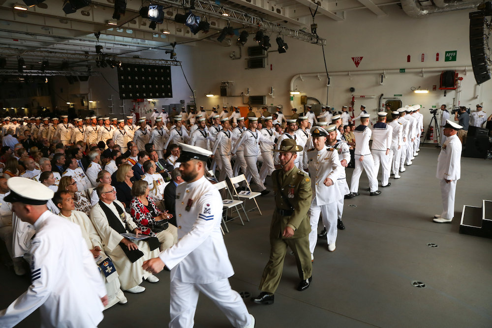 HMAS Adelaide's Ship's Company marches out during their Commissioning ceremony, alongside Garden Island, Sydney
