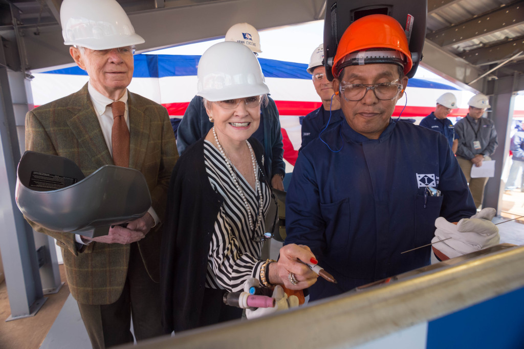 Ship Sponsor Kay Webber Cochran (center) sketches her initials onto the keel plate of the National Security Cutter Kimball (WMSL-756). Also pictured are her husband, Senator Thad Cochran (left), R-Mississippi, and Ingalls Shipbuilding employee Jerry Wesley (right), who welded the initials onto the plate (Photo by Lance Davis/HII)
