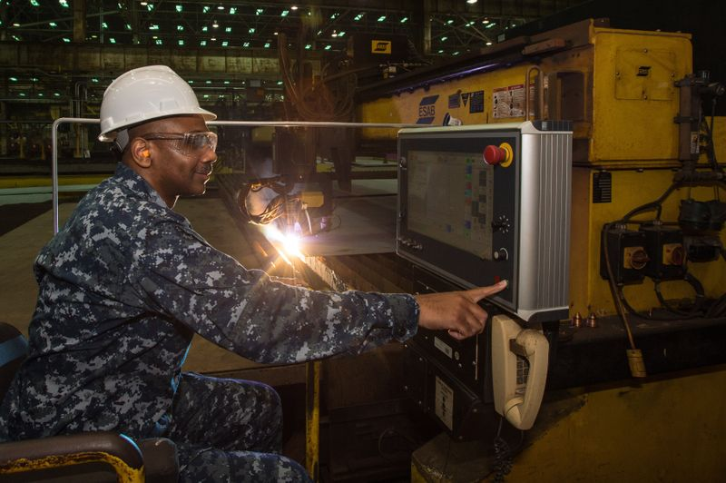 Commander Dave Murray, production officer for the U.S. Navy's DDG-51 program, presses the button to start fabrication of the Ingalls-built destroyer USS Frank E. Petersen Jr. (DDG-121) (Photo by Lance Davis/HII)