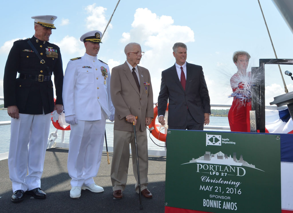 Ship Sponsor Bonnie Amos christens the amphibious transport dock Portland (LPD-27), accompanied by (left to right) U.S. Marine Corps Major General Christopher Owens, director of the U.S. Navy's expeditionary warfare division; Captain Jeremy Hill, prospective commanding officer, Portland; Ted Waller, a World War II veteran who served on the first USS Portland (CA-33); and Brian Cuccias, president of Ingalls Shipbuilding (Photo by Lance Davis/HII)