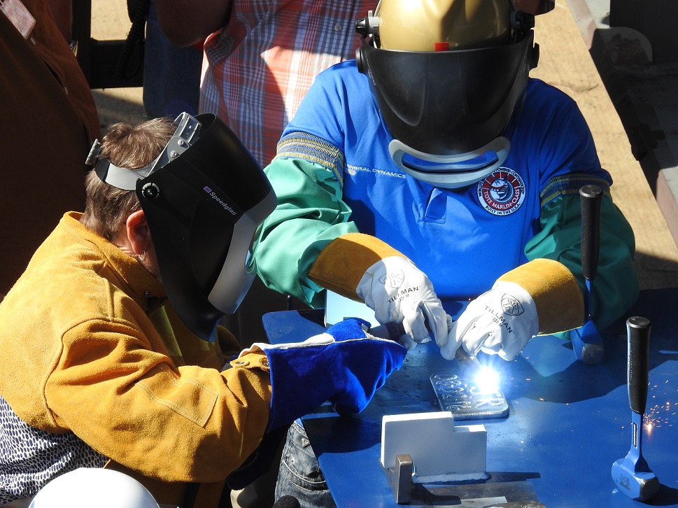 Ms. Travie Ross welds her initials onto the keel