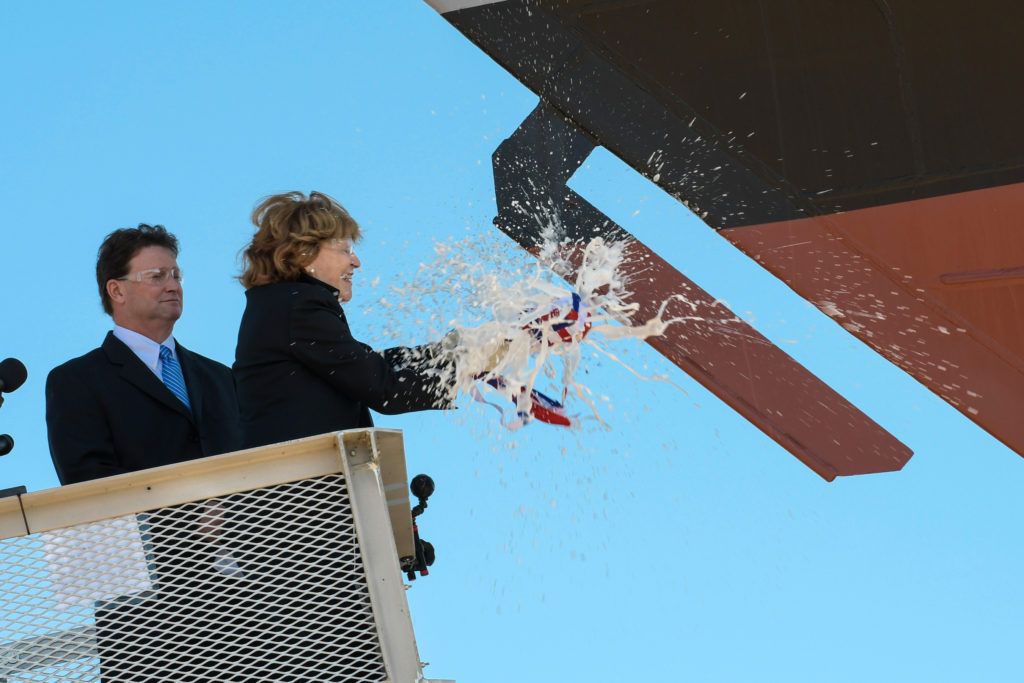 Ship sponsor Kate Lehrer breaks a bottle of champagne across the bow during the christening ceremony for the nation's 13th Littoral Combat Ship, the future USS Wichita, at the Fincantieri Marinette Marine shipyard on September 17
