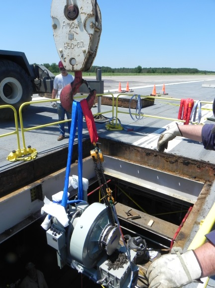 The Advanced Arresting Gear team guides an electric motor as it is lowered into the pit at the Runway Arrested Landing Site (RALS). The team has been working for months to prepare the site for commissioning and live aircraft arrestment testing slated for late 2015 (U.S. Navy photo)
