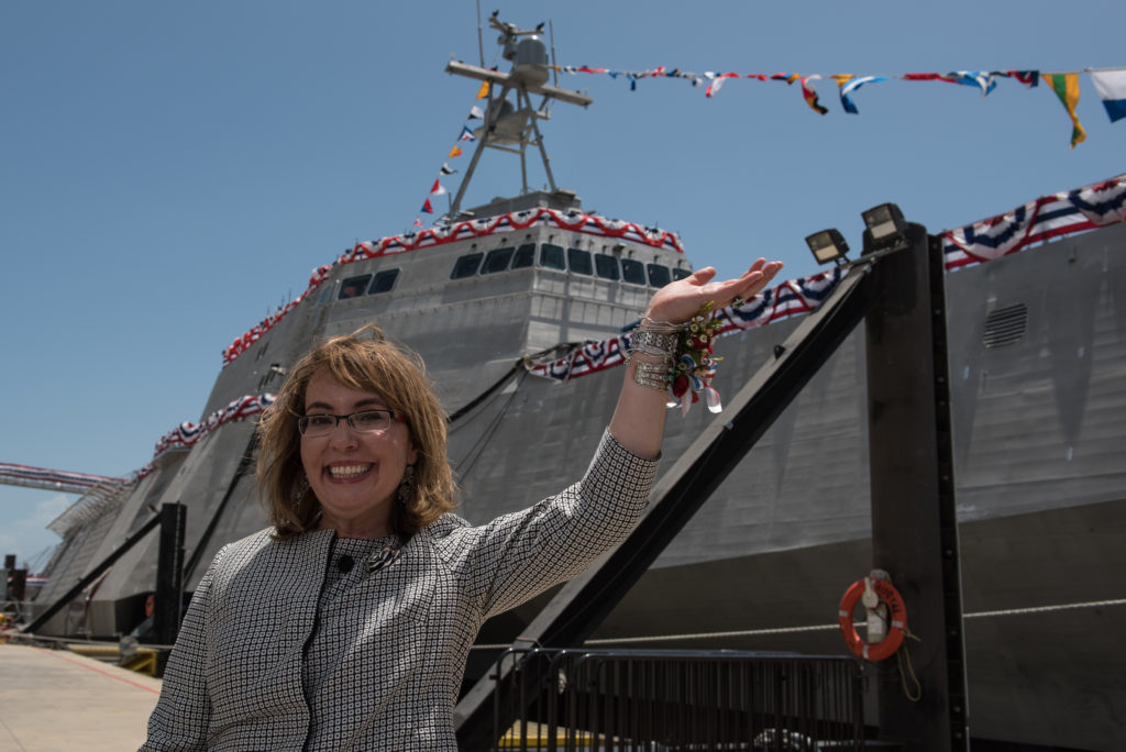 Former U.S. Representative Gabrielle «Gabby» Giffords waves to a crowd in front of the littoral combat ship, USS Gabrielle Giffords (LCS-10), named for her. Giffords was on the stage as Dr. Jill Biden christened the ship at Austal USA in Mobile, Alabama. The 419-foot/127.7 м ship was built at the Austal shipyard and is the U.S. Navy's 10th littoral combat ship designed to operate in shallow waters near the coast. It is 16th U.S. naval ship to be named for a woman and only the 13th since 1850 to be named for a living person (Photo courtesy Austal USA/Released)