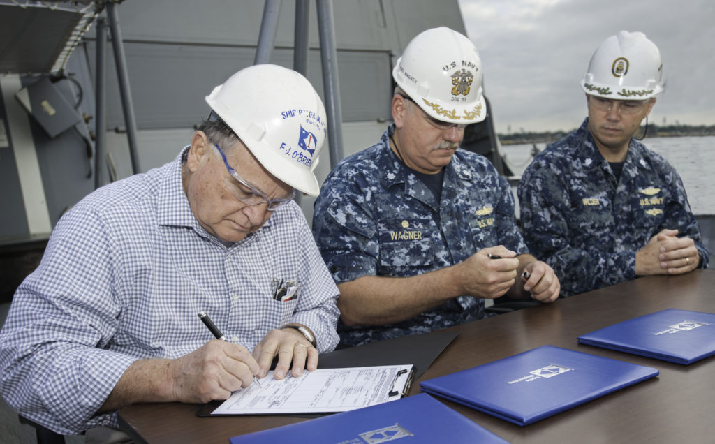 Delivery of the Aegis guided missile destroyer USS John Finn (DDG-113), named for a Pearl Harbor hero and the Navy's first World War II Medal of Honor recipient, was officiated on the 75th anniversary of the attack on Pearl Harbor, December 7, 2016. Signing the document are, from left, Freddie Joe O'Brien, Ingalls' DDG-113 ship program manager; Navy Commander Micheal Wagner, prospective commanding officer of DDG-113; and Commander Ben Wilder, former Navy DDG-51 program manager's representative (Photo by Lance Davis/HII)