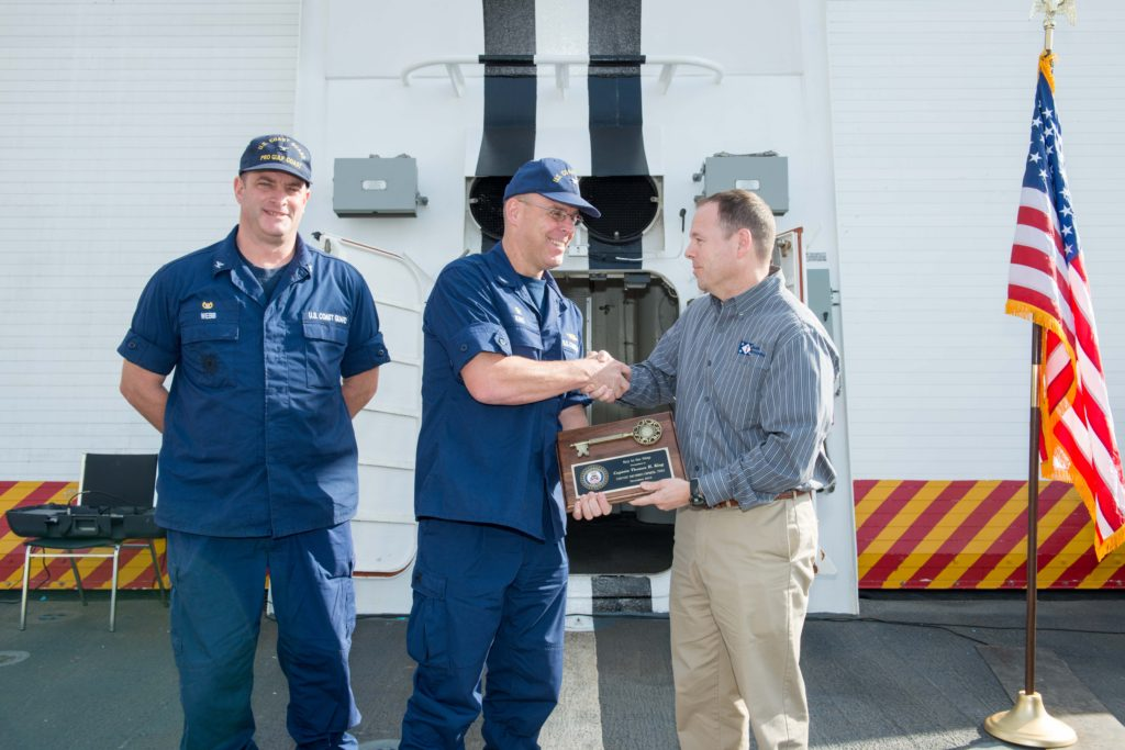 Derek Murphy (right), Ingalls' NSC program manager, presents the key plaque to Captain Thomas King, Munro's commanding officer, with Christopher Webb, commanding officer of the U.S. Coast Guard's Project Resident Office Gulf Coast, observing (Photo by Andrew Young/HII)