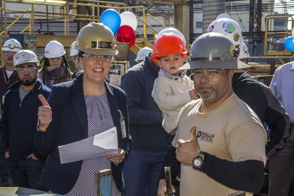The ceremony's honoree, Jackie Ruiz, gives her sign of approval after inspecting the first cut of steel for the ESB-5 as her son watches in the background. Jackie is the wife of Bryan Ruiz, NASSCO's Director of Planning, and is also a former NASSCO employee