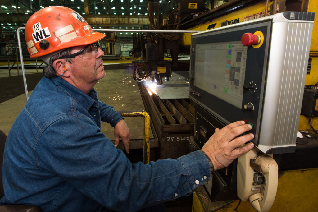 Paul Bosarge, a steel fabrication burner at Ingalls Shipbuilding, presses the button to start fabrication of the Ingalls-built destroyer USS Lenah H. Sutcliffe Higbee (DDG-123). Bosarge has worked at Ingalls for 39 years (Photo by Lance Davis/HII)