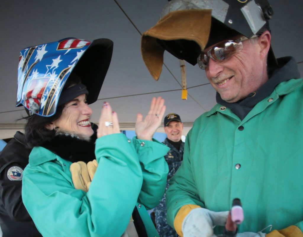Luci Baines Johnson applauds Timothy Trask, a Bath Iron Works welder, after he helped her authenticate the keel plate of DDG-1002, the future USS Lyndon B. Johnson, by striking an arc to her initials engraved in the plate. She was at BIW with her sister, Lynda Johnson Robb, as the two participated in the keel laying ceremony for the third destroyer in the Zumwalt class