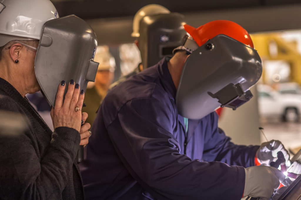 Jeremy Lally, a structural welder at Ingalls Shipbuilding, welds the initials of ship sponsor D'Arcy Neller (left) onto the keel plate of the destroyer USS Frank E. Petersen Jr. (DDG-121) (Photo by Lance Davis/HII)