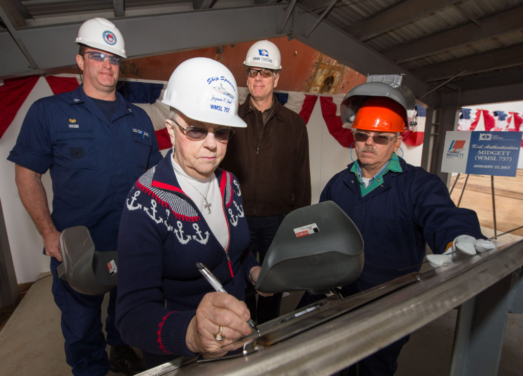 Ship Sponsor Jazania O'Neal writes her initials onto a steel plate that will be welded inside USCGC Midgett (WMSL-757), the National Security Cutter named in honor of her grandfather, John Allen Midgett. Pictured with O'Neal are (left to right) Capt. Christopher Webb, commanding officer, U.S. Coast Guard Project Resident Office Gulf Coast; Ingalls Shipbuilding President Brian Cuccias; and Jack Beard, a structural welder at Ingalls (Photo by Lance Davis/HII)