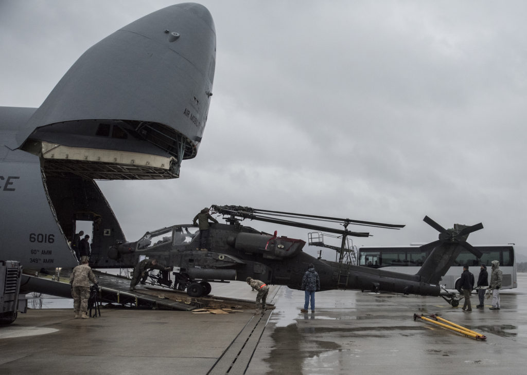 An AH-64 Apache helicopter is unloaded from a C-5M Galaxy airplane at Ramstein Air Base, Germany, February 22 in support of Operation Atlantic Resolve (Photo Credit: SSG Tamika Dillard, U.S. Army Europe Public Affairs)