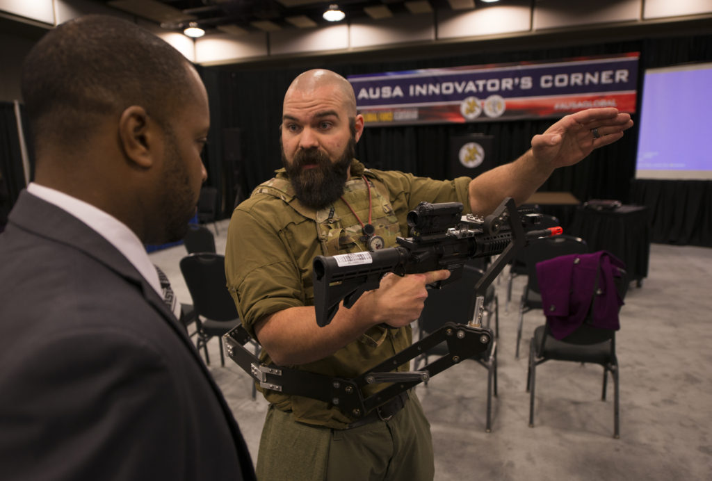 Zac Wingard, a mechanical engineer at the Army Research Laboratory, explains the «third arm» body-worn weapon mount during the Association of the United States Army's Global Force Symposium in Huntsville, Alabama, March 14, 2017. The lab is developing the device that could lessen Soldier burden and increase lethality (Photo Credit: Sean Kimmons)