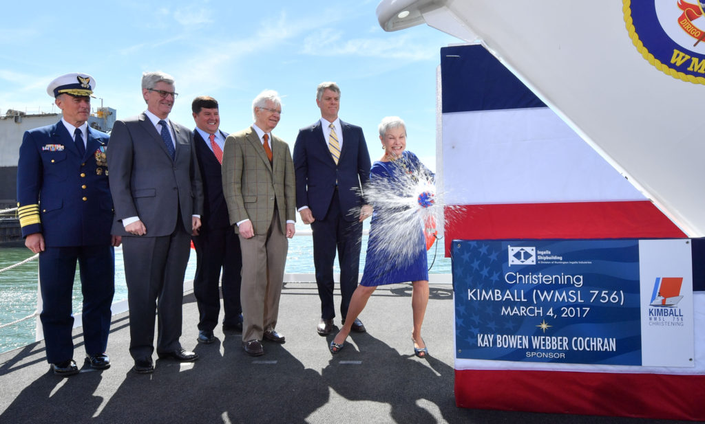 Ship's sponsor Kay Webber Cochran smashes a bottle of sparkling wine against the bow of the Ingalls-built National Security Cutter USCGC Kimball (WMSL-756). Also pictured (left to right) are U.S. Coast Guard Commandant Admiral Paul Zukunft; Mississippi Governor Phil Bryant; Representative Steven Palazzo, Republican-Mississippi; Senator Thad Cochran, Republican-Mississippi; and Ingalls Shipbuilding President Brian Cuccias (Photo by Lance Davis/HII)
