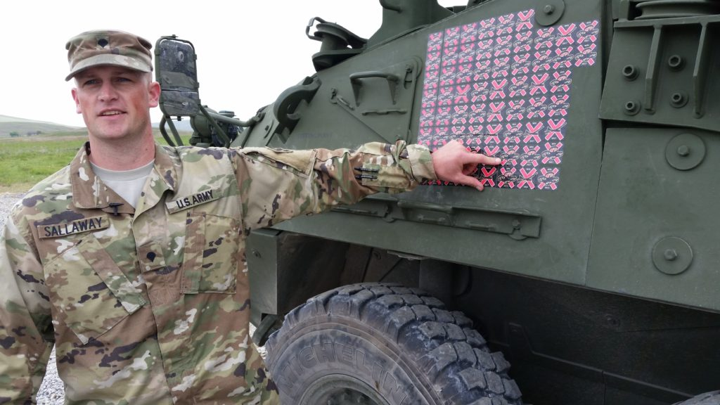 Specialist Brandon Sallaway, a fire support specialist and forward observer from Fort Carson, Colo., points to a sticker on the side of the Mobile High-Energy Laser-equipped Stryker he helped evaluate, April 12, at the 2017 Maneuver Fires Integrated Experiment at Fort Sill, Okla. The stickers represent the number of drones the MEHEL has shot out of the sky using a 5-kW laser. Sallaway was the first Soldier to actually use the MEHEL to take down a target (Photo Credit: C. Todd Lopez)