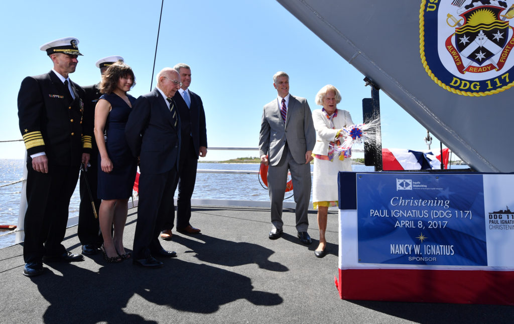 Ship's Sponsor Nancy Ignatius christens DDG-117, the destroyer named for her husband, Paul Ignatius, former Secretary of the Navy. Also pictured (left to right) are Chief of Naval Operations Admiral John M. Richardson; Commander Robby Trotter, the ship's prospective commanding officer; Doctor Elisa Ignatius, granddaughter of Paul and Nancy Ignatius; Paul Ignatius, the ship's namesake; Philip Gunn, Speaker of the Mississippi House of Representatives; and Ingalls Shipbuilding President Brian Cuccias (Photo by Andrew Young/HII)