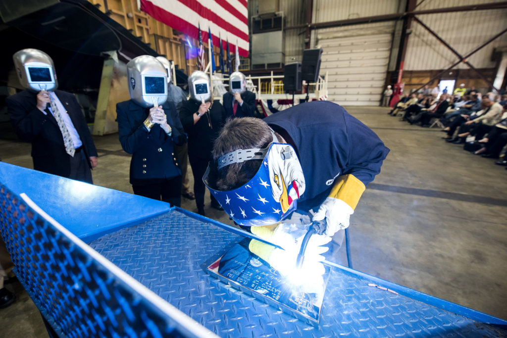 A welder authenticates the keel of LCS-19, the future USS St. Louis, by welding the initials of ship sponsor Barbara Broadhurst Taylor. The Keel Laying is the formal recognition of the start of the ship's module construction process
