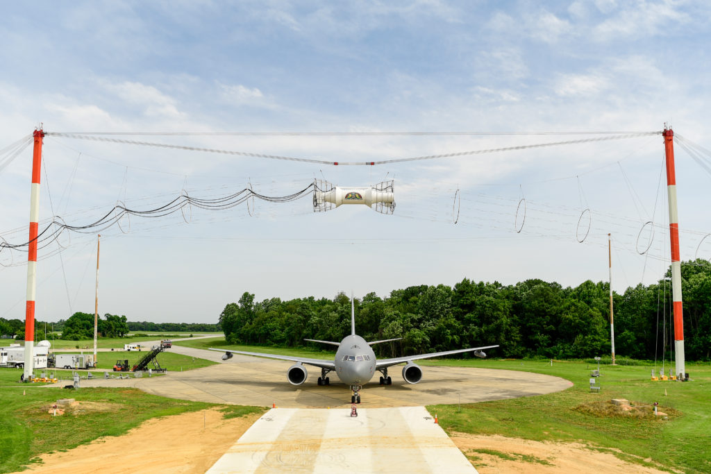 A Boeing KC-46A Pegasus tanker undergoes testing at Naval Air Station Patuxent River, Maryland, on the base's electromagnetic pulse pad. In order to evaluate its ability to operate safely through electromagnetic fields produced by radar, radio towers and other systems, the aircraft received a series of pulses from a large coil mounted overhead. The KC-46 is protected by technologies designed into the aircraft to negate any effects (Photo credit: NAVAIR photographer)