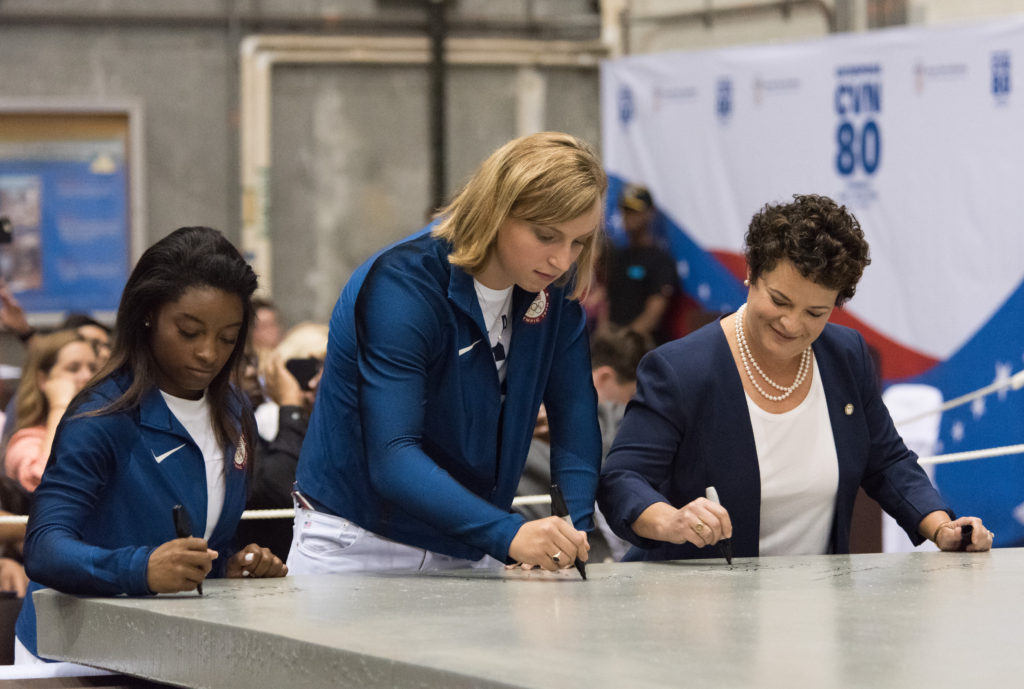 Ship's Sponsors and U.S. Olympic gold medalists Simone Biles (left) and Katie Ledecky (center) join Newport News Shipbuilding President Jennifer Boykin in signing a 35-ton steel plate that will be part of the foundation of the new Gerald R. Ford-class aircraft carrier USS Enterprise (CVN-80) (Photo by Matt Hildreth/HII)