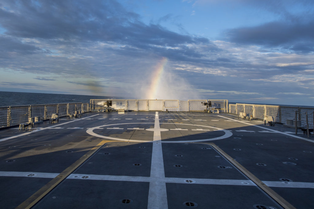 A rainbow is visible in LCS-9's «rooster tail» during Builder's Sea Trials on Lake Michigan. At top speed, LCS-9's four water jets move approximately 2 million gallons/7.5 million liters of water per minute producing a 30-foot/9.1-meter wall of water known as a rooster tail. That's enough water to fill an Olympic swimming pool in 20 seconds