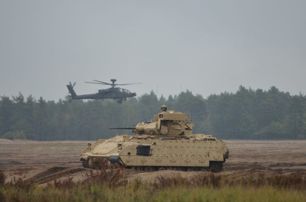 Apache helicopters from the 1st Attack Reconnaissance Battalion, 501st Aviation Regiment, Combat Aviation Brigade, regroup at a new battle position with Bradley Fighting Vehicles and Abrams tanks from the 5th Squadron, 4th Cavalry Regiment, 2nd Armored Brigade Combat Team, during a readiness demonstration, Presidenski Range, Trzebian, Poland, September 25. The combined arms live-fire is a demonstration of the unit's capability and to ensure equipment is still in working conditions. The unit is in Poland to support Atlantic Resolve, a U.S. endeavor to fulfill NATO commitments by rotating U.S.-based units throughout the European theater and training with NATO partners and Allies (U.S. Army photo by Sergeant Shiloh Capers)