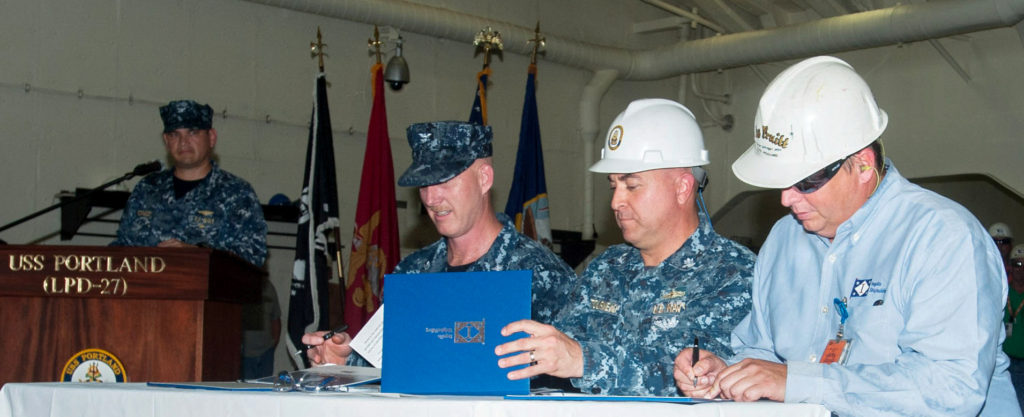 (Left to right) Captain J.R. Hill, Commander Jon Letourneau and Mike Pruitt sign the DD 250 document officially transferring custody of the amphibious transport dock USS Portland (LPD-27) from HII to the U.S. Navy. Hill is Portland's prospective commanding officer; Letourneau is the Navy's LPD 17-class program manager, and Pruitt is Ingalls' LPD 27 program manager (Photo by Michael Duhe/HII)
