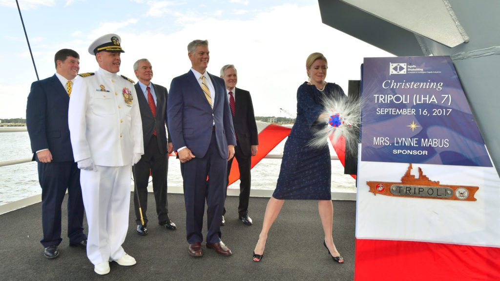 Lynne Mabus, wife of former Secretary of the Navy Ray Mabus, is the ship's sponsor and officially christened Tripoli after successfully breaking a bottle of sparkling wine across its bow
