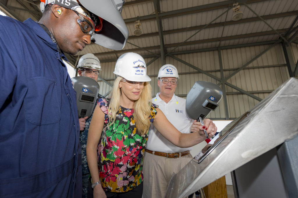 Ship's Sponsor Meredith Berger traces her initials onto a steel plate that will be welded inside the amphibious transport ship USS Fort Lauderdale (LPD-28). Pictured with Berger are (left to right) Howard Sparks, a structural welder at Ingalls; Captain Brian Metcalf, the U.S. Navy's LPD 17-class program manager; and Steve Sloan, Ingalls' LPD program manager (Photo by Lance Davis/HII)