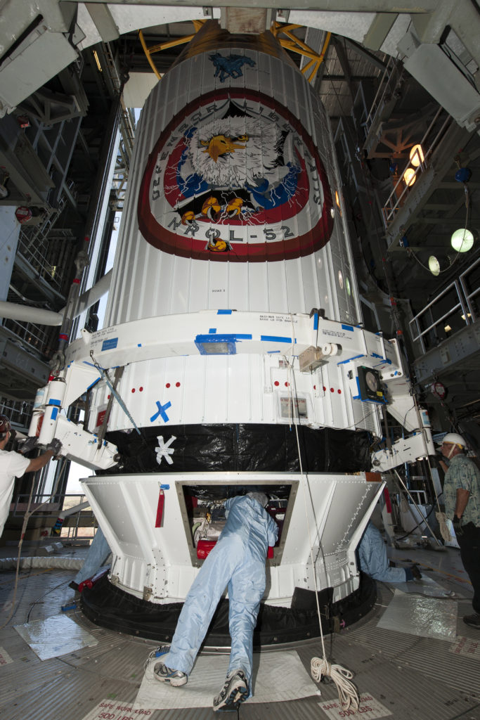 A 4-meter diameter payload fairing, with the National Reconnaissance Office's NROL-52 mission encapsulated inside, is mated to an Atlas V rocket at the Vertical Integration Facility at Cape Canaveral's Space Launch Complex-41