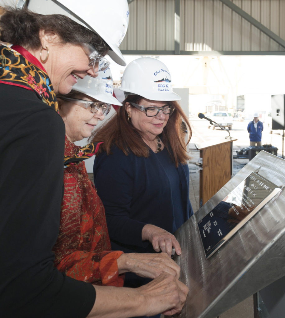 Ship's Sponsors (left to right) Virginia Munford, Louisa Dixon and Pickett Wilson trace their initials onto a steel plate that will be welded inside the guided missile destroyer USS Lenah H. Sutcliffe Higbee (DDG-123) (Photo by Michael Duhe/HII)