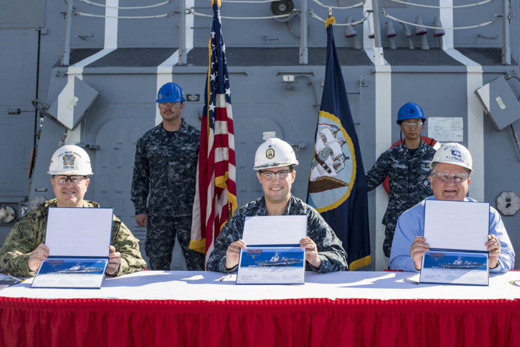 Ingalls Shipbuilding delivered the guided missile destroyer USS Ralph Johnson (DDG-114) to the U.S. Navy on November 15, 2017. Signing the DD 250 document are (left to right) Commander Jason P. Patterson, the ship's prospective commanding officer; Commander Scott Williams, program manager representative for Supervisor of Shipbuilding Gulf Coast; and Freddie Joe O'Brien, Ingalls' DDG-114 ship program manager (Photo by Andrew Young/HII)