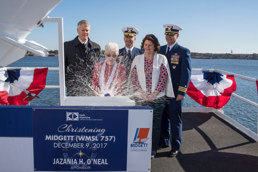 Ship's Sponsor Jazania H. O'Neal smashes a bottle of sparkling wine against the bow of the National Security Cutter USCGC Midgett (WMSL-757). Also pictured (left to right) are Ingalls Shipbuilding President Brian Cuccias; Coast Guard Vice Commandant Admiral Charles Michel; Matron of Honor Jonna Midgette; and Captain Anthony Williams, the ship's prospective commanding officer (Photo by Andrew Young/HII)