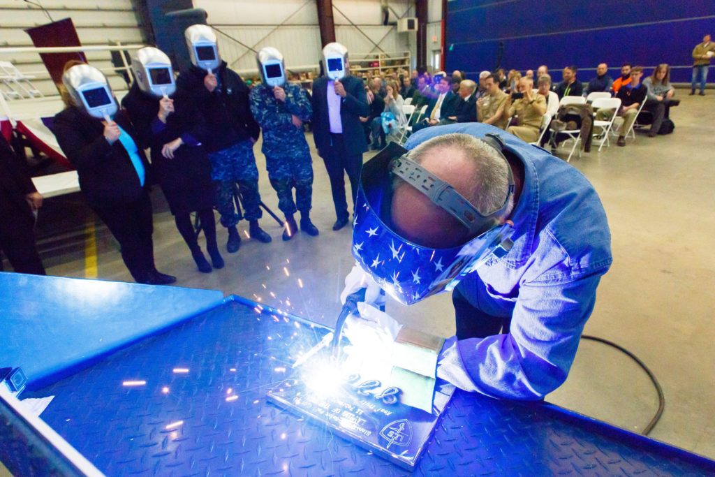 A welder authenticates the keel of LCS-21, the future USS Minneapolis-Saint Paul, by welding the initials of ship sponsor Jodi J. Greene. The Keel Laying is the formal recognition of the start of the ship's module construction process
