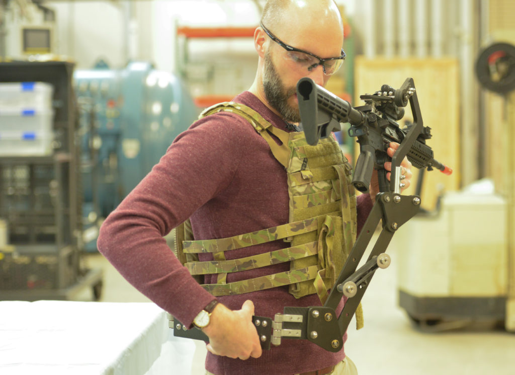 Army Research Lab engineer Dan Baechle demonstrates how to strap on the «Third Arm», a mechanical device designed to improve Soldiers' accuracy and reduce fatigue (Photo Credit: U.S. Army photo by Joe Lacdan)